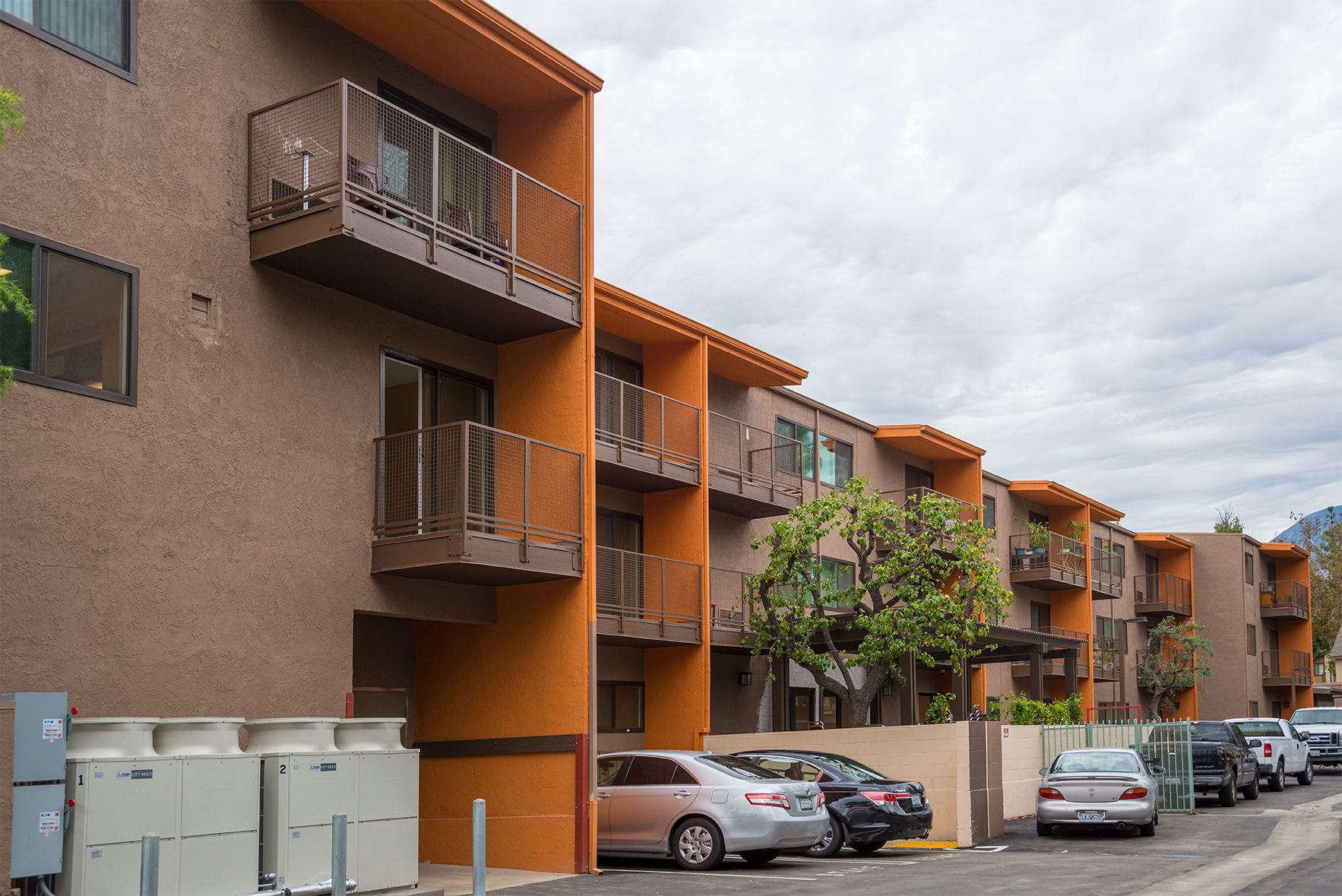 Apartment Building side view showcasing Orange color with Brown colors as well. Railings and Power generators depicted as well.