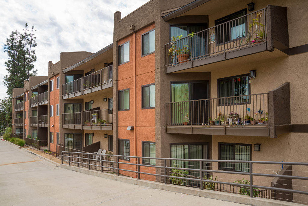 Apartment Building side view showcasing Orange color with Brown colors as well. Railings depicted as well.